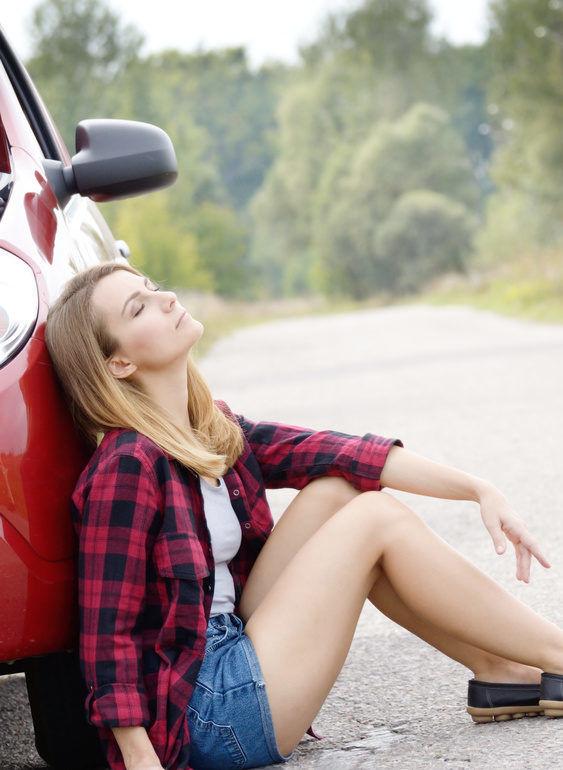Frau sitzt am Auto